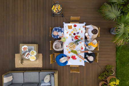 Group of senior friends sitting by the table and eating during garden party