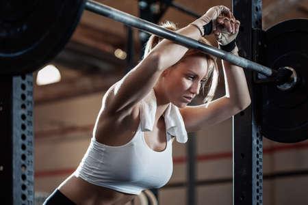 Zmęczona ładna dziewczyna odpoczywa po podnoszeniu ciężarów w centrum fitness