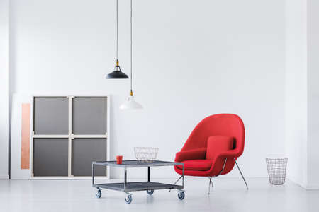 Red armchair and metal coffee table in a modern daily room interior. Real photo