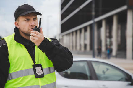 Proud policemen speaking on the walkie-talkie, reporting to station