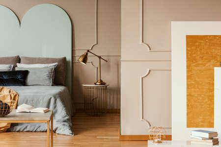 Lampe dorée sur une table de chevet moderne à côté d'un lit bleu à l'intérieur de la chambre grise