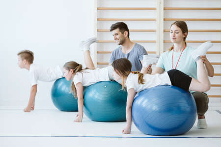 Cute group of kids exercising with balls during sport lesson at school