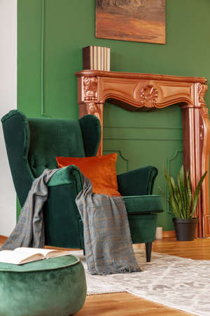 Emerald green wing back chair with orange pillow in luxury living room interior Standard-Bild