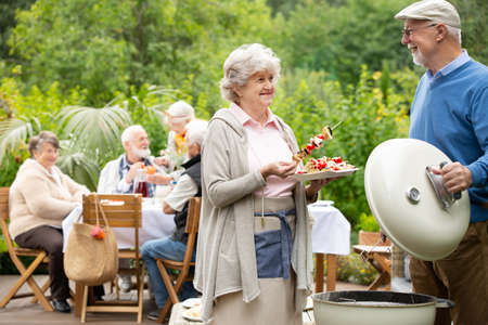 Older happy woman serving skewers during barbecue party in the garden Zdjęcie Seryjne