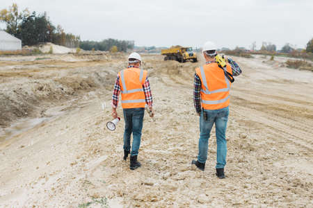 Two professional road construction workers in orange vests and protective helmets in the middle on the terrain