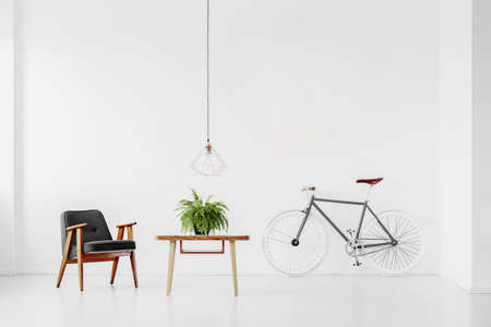 Retro armchair and table with a plant in a white room interior with a bike. Real photo Stock fotó