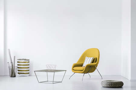 Real photo of a minimalistic living room interior with a yellow armchair. Empty, white wall. Place your poster Stock fotó