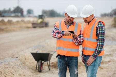 Two builders checking road construction plan on the phone Stock Photo