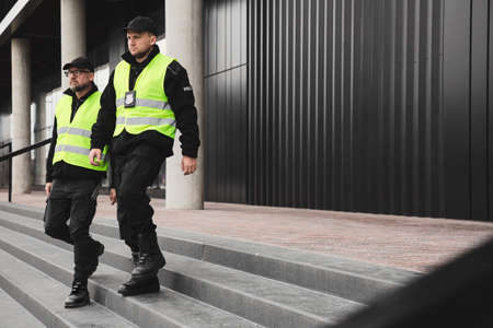 Policemen in reflective vests looking around carefully during patrol in the city center