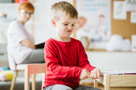 Kleiner Junge, der im Klassenzimmer spielt, während sein Therapeut ihn beobachtet