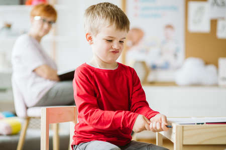 Little boy playing in the classroom while his therapist observes him