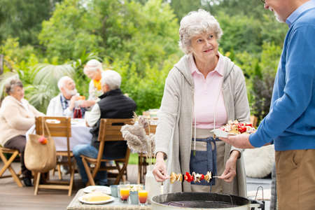 Senior man and woman talking by barbecue during the garden party