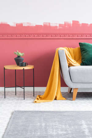 Trendy small vase on wooden coffee table next to grey sofa with yellow blanket