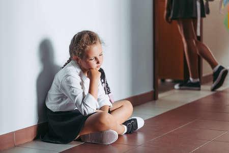 Sad young girl sitting alone on a school corridor during break