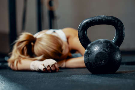 Young exhausted girl lying on a floor of fitness center after training Zdjęcie Seryjne