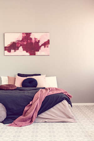 Abstract amaranth and pastel pink painting above king size bed with pink and black bedding