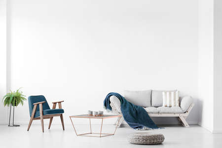 Real photo of a bright living room interior with a sofa, armchair and coffee table. Empty wall, place your painting Stock fotó