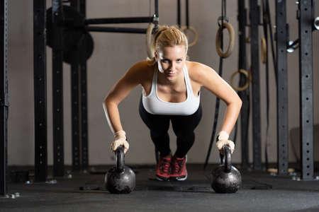 Jonge vrouw met sterke handen die traint bij professioneel crossfitcentrum