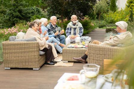 Group of older people sitting on a terrace at friends house