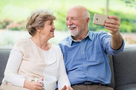 Cute senior couple taking selfie at home for social media