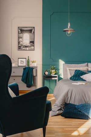 Copy space on empty green wall of elegant bedroom interior