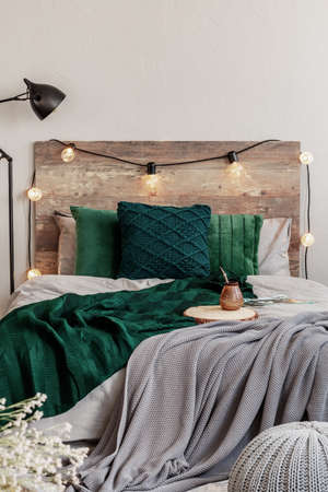 Emerald green pillows and blanket on wooden king size bed with grey bedding Zdjęcie Seryjne