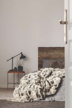 Wooden and grey bedroom design with rustic headboard, copy space on empty wall Zdjęcie Seryjne