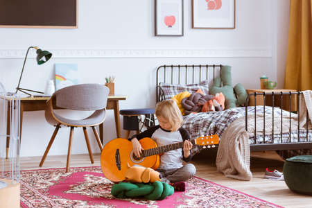 Cute blond girl sitting on the floor of her trendy bedroom,learning how to play a guitar