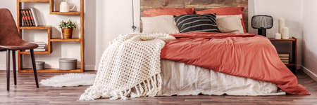 Panoramic view of trendy bedroom in rustic style with king size bed with dirty orange bedding