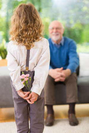 Cute blond child standing with flowers behind her back on the grandfathers day