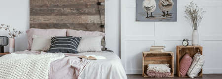 Panoramic view of trendy bedroom in rustic style with wooden boxes as nightstand tables