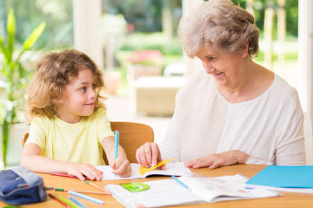 Smiling grandmother drawing with crayons with a young grandson Zdjęcie Seryjne