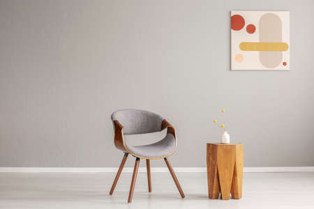 Stylish grey wooden chair in empty living room interior with trendy wooden coffee table