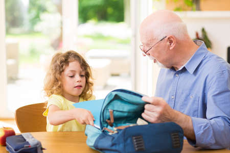 Grandfather and grandson are packing a backpack for school Zdjęcie Seryjne