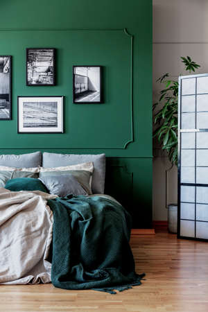 Gallery of black and white posters and photos on emerald green wall in trendy bedroom Zdjęcie Seryjne