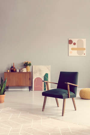Green retro armchair in grey living room interior with wooden furniture