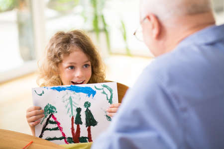 Cute little boy showing his painting to grandfather