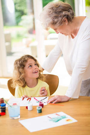 Grandmother painting a picture with paints with her grandson Zdjęcie Seryjne