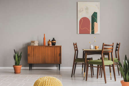 Vintage grey dining room with abstract paintings and wooden cupboard