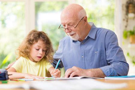 Grey grandfather and his cute grandson do homework
