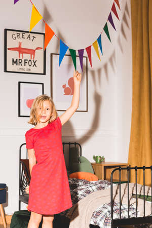 Cute blond girl in red dress standing in the middle of her trendy bedroom