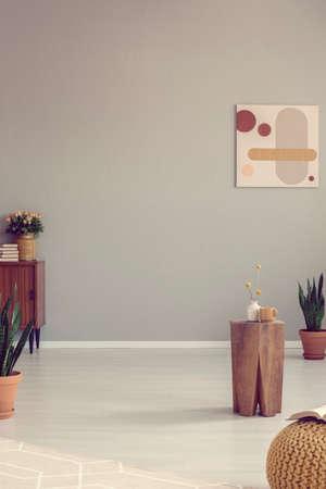 Empty grey room with stylish wooden table with vases Zdjęcie Seryjne