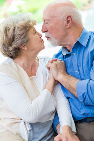 Adorable senior marriage holding hands and kissing