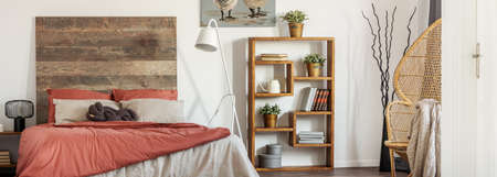 Panoramic view of peacock chair, fancy wooden bookshelf and king size bed with headboard in trendy bedroom in rustic style Zdjęcie Seryjne