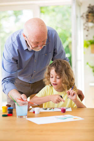 Grandfather painting a picture with paints with his grandson