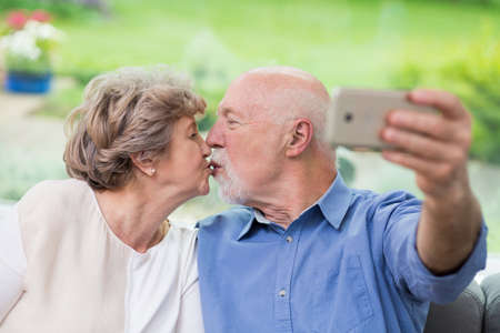 Cute elderly couple kissing in front of a mobile phone while taking selfie Zdjęcie Seryjne