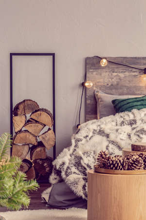 Pie of wood in metal stand next to king size bed with wooden headboard with light bulbs