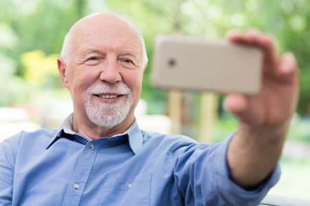 Adorable grandfather taking selfie with his mobile phone Zdjęcie Seryjne
