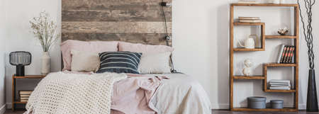 Panoramic view of comfortable bed with pastel pink sheets and white blanket in trendy bedroom in rustic style