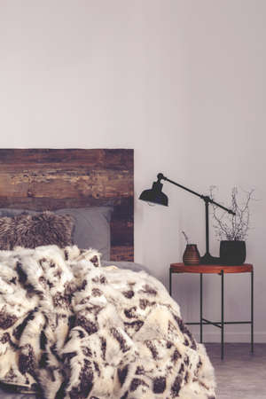 Yerba Mate and black industrial lamp on elegant wooden nightstand next to cozy bed with fury blanket